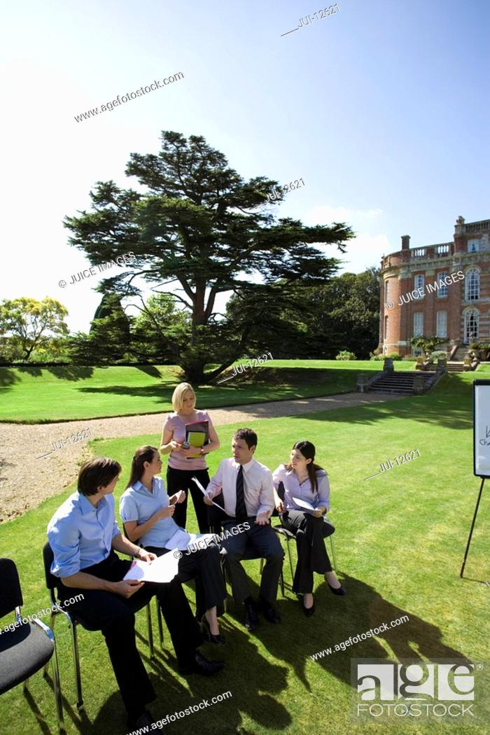 Stock Photo: Businessmen and women on chairs on grass by manor house, in training course, elevated view.