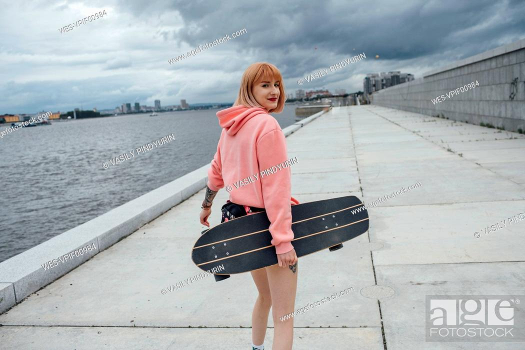 Stock Photo: Young woman holding skateboard walking at the riverside.