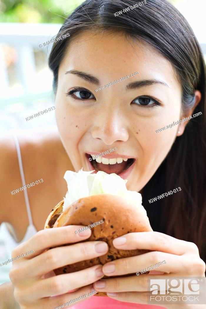 Stock Photo: Portrait of a young woman eating burger.
