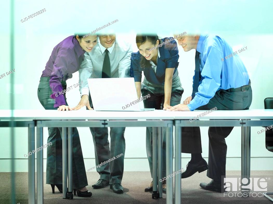 Stock Photo: Four businesspeople in office looking at laptop.