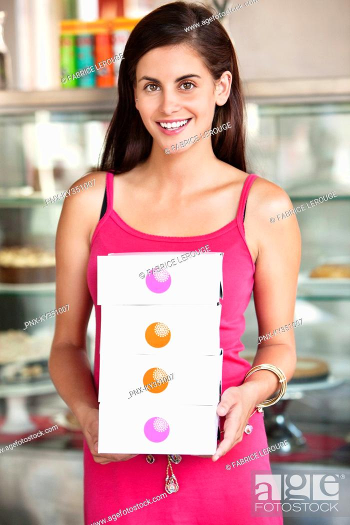Stock Photo: Smiling woman holding cake boxes in a bakery.