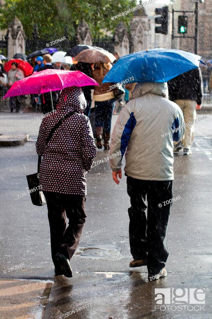Stock Photo: Menschen überqueren am Fußgängerüberweg die Straße, während es regnet.