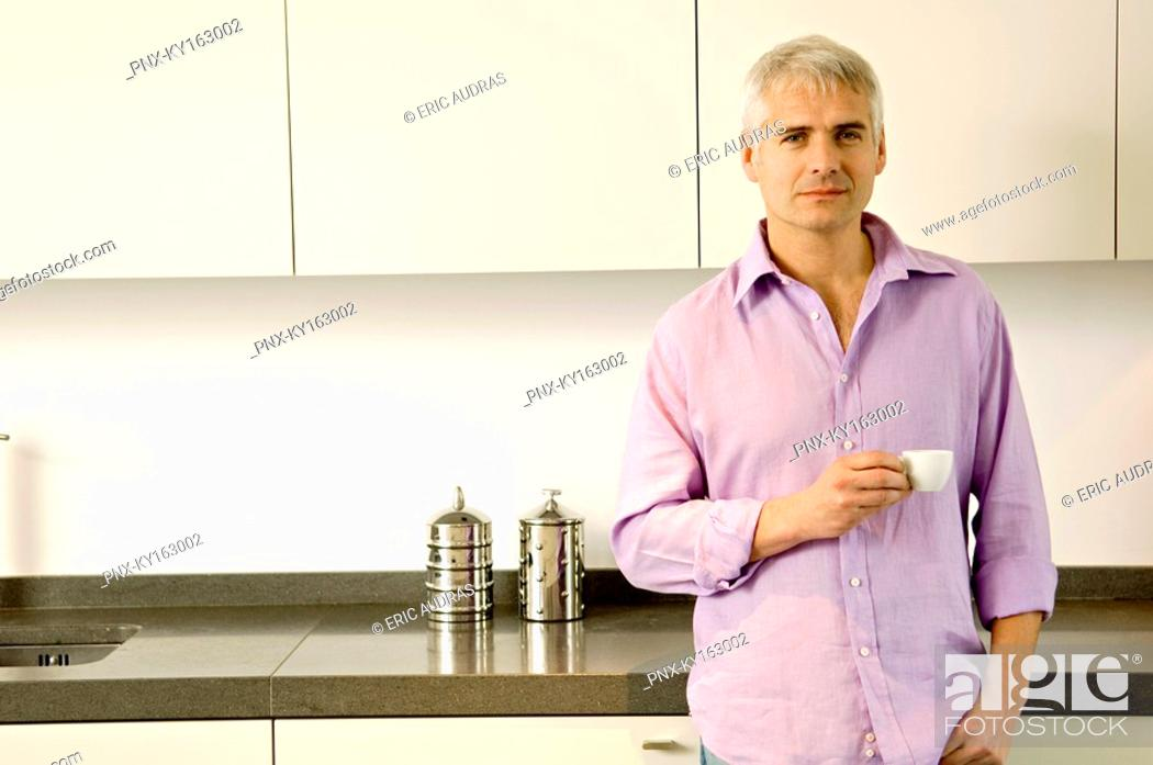 Stock Photo: Portrait of a mature man holding a cup of tea in the kitchen.