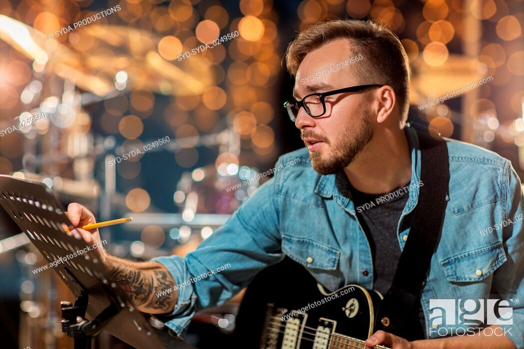 Stock Photo: man with guitar writing to music book at studio.