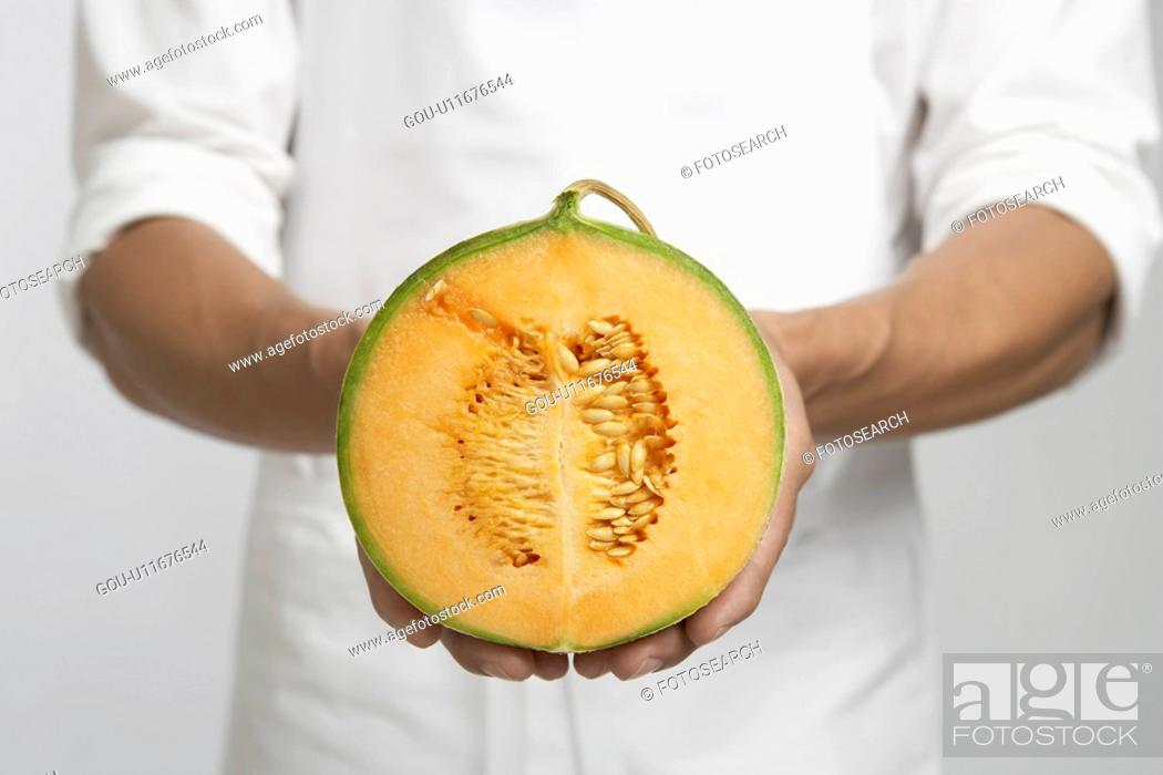Stock Photo: Chef holding half of cantaloupe melon (mid section).