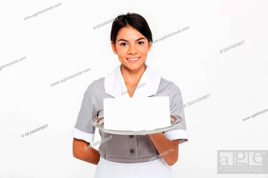 Photo de stock: Portrait of ypung smiling female waiter in uniform holding metal tray with empty invitation while standing and looking at camera, isolated over white background.