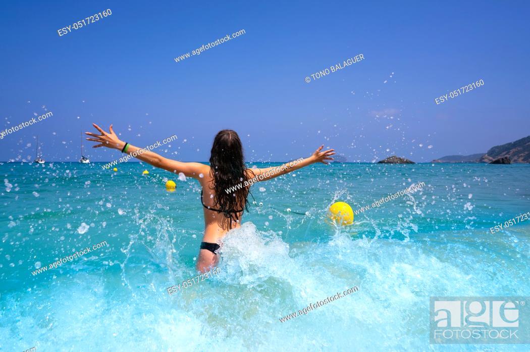 Stock Photo: Ibiza beach girl splashing water open arms in Balearic islands.