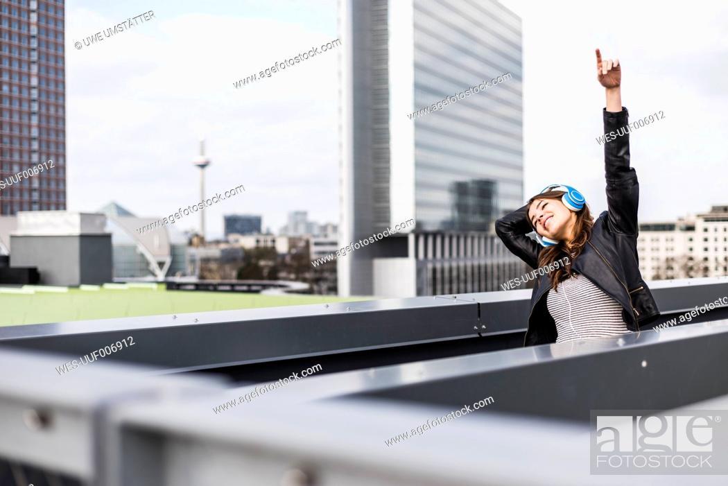 Imagen: Young woman in the city wearing headphones, dancing.