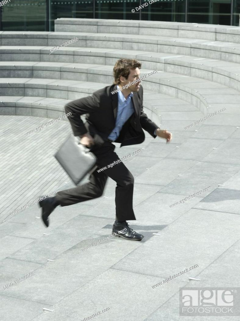 Stock Photo: Businessman with briefcase running up steps outdoors side view.