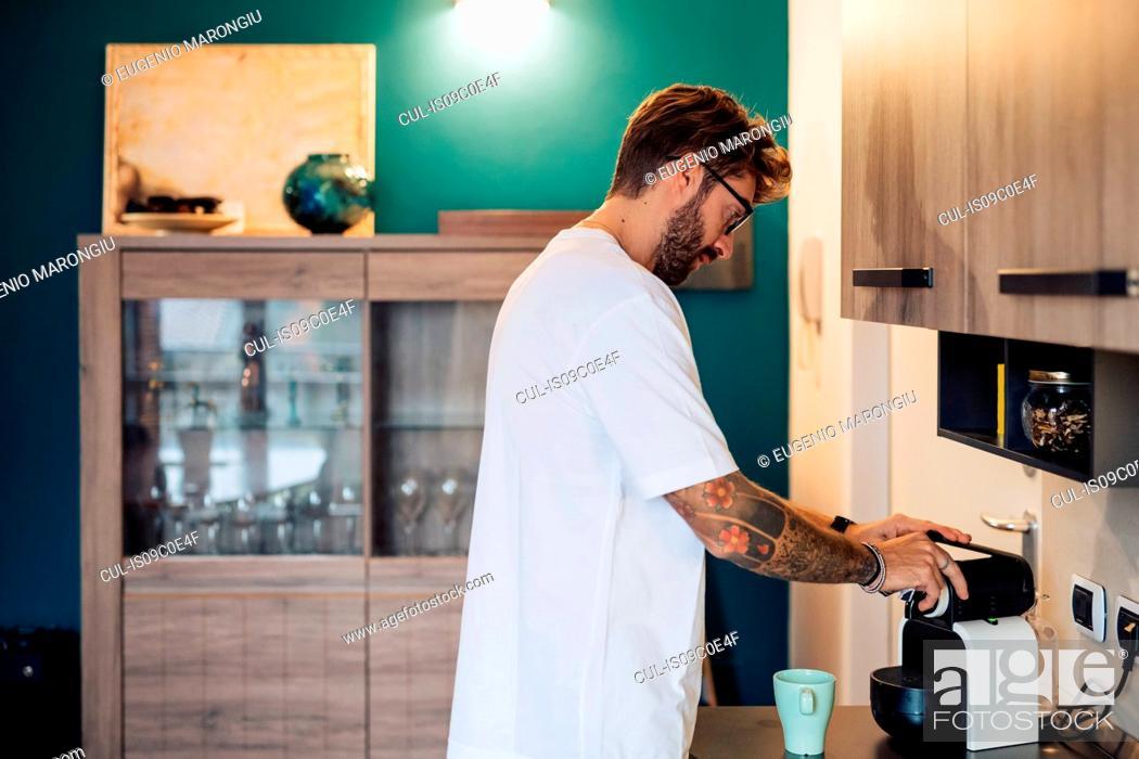 Stock Photo: Mid adult man preparing coffee machine on kitchen counter.