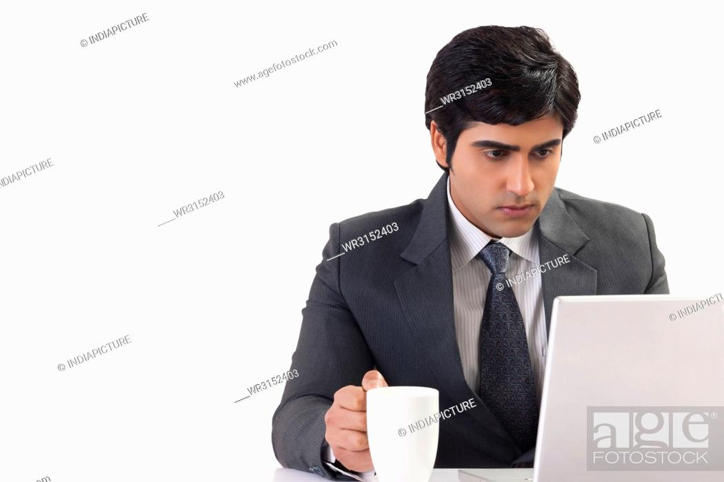 Photo de stock: Businessman holding coffee cup working on desk at office.