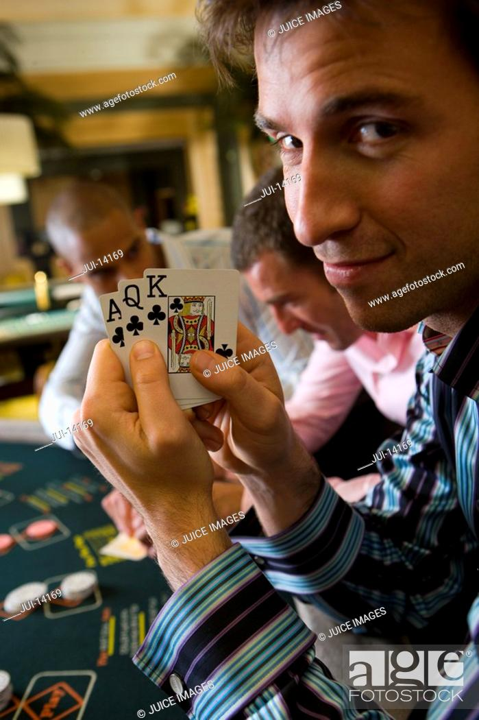 Stock Photo: Young man gambling at poker table in casino, showing cards, smiling, portrait.