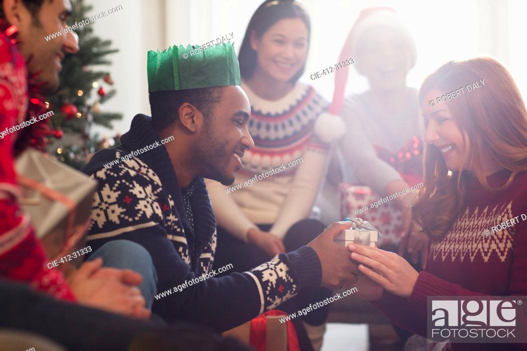 Stock Photo: Friends watching boyfriend giving Christmas gift to girlfriend.