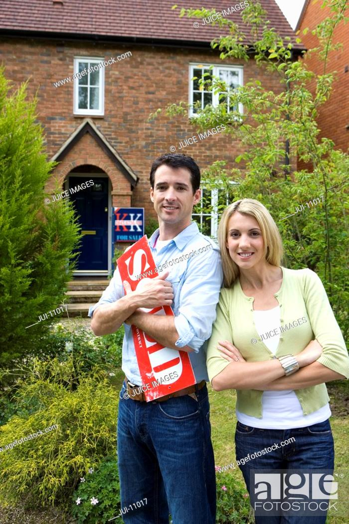 Stock Photo: Young couple outside house, man with 'sold' sign, smiling, portrait.