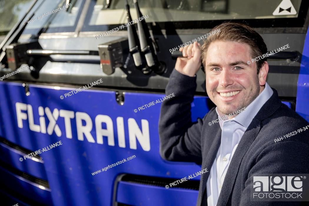 Stock Photo: 23 May 2019, North Rhine-Westphalia, Cologne: Fabian Stenger, Managing Director of FlixTrain, squats on the locomotive at Berlin-Südkreuz station before the.