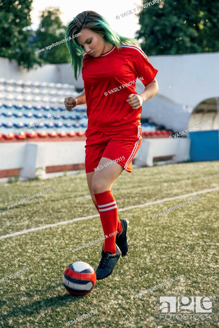 Photo de stock: Young woman playing football on football ground dribbling with the ball.