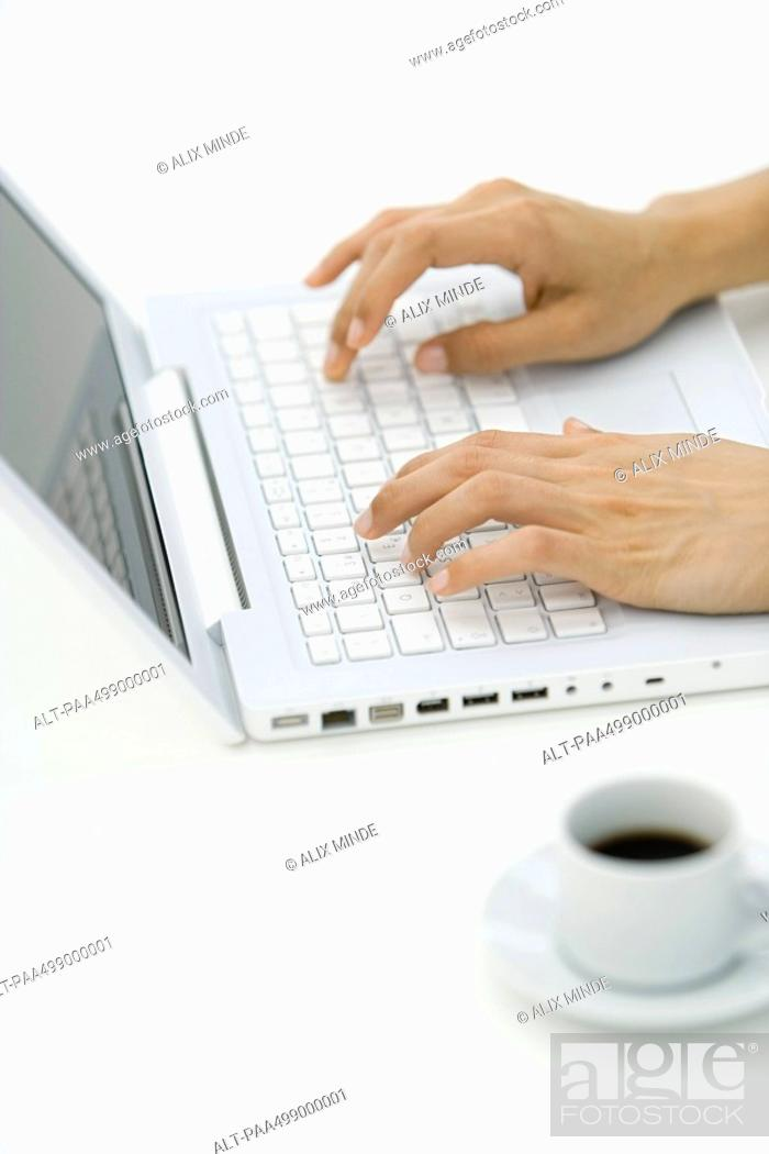 Stock Photo: Hands typing on laptop computer, coffee cup in foreground.