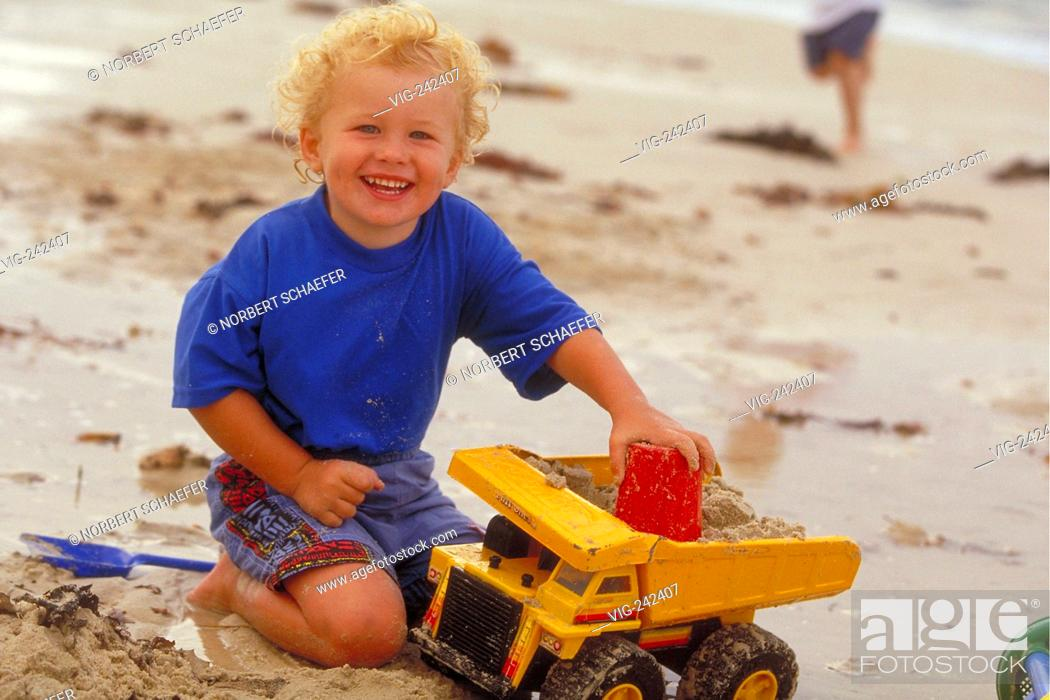 afa052d41 Stock Photo - portrait, full-figure, outdoor, 2-year-old blond curly boy  wearing a blue t-shirt plays with a yellow toy truck in the sand at the  beach ...