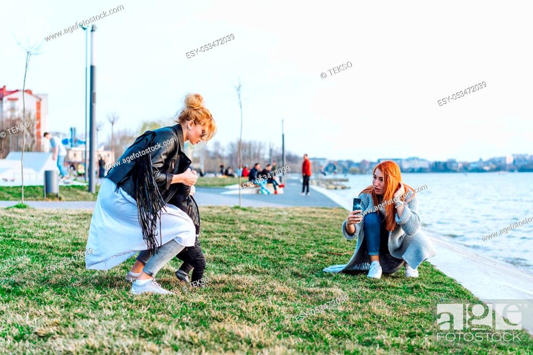 Stock Photo: Beautiful happy family on the lake. Two women - mom and aunt play with a boy.
