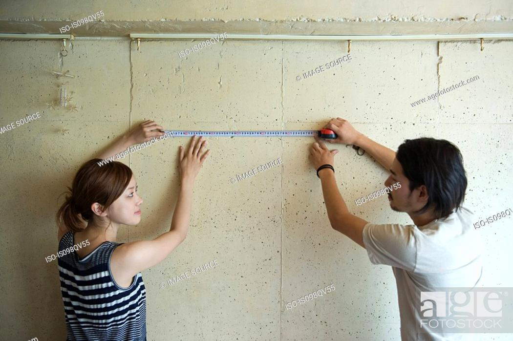 Stock Photo: Young couple measuring wall.