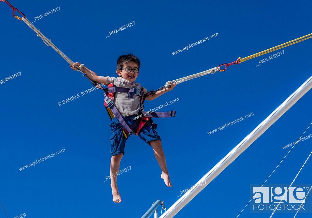Imagen: Five-year-old boy doing bungee trampoline.