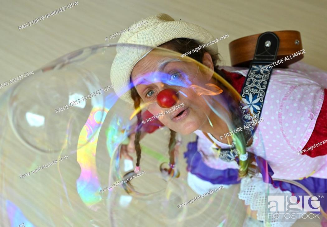 "Stock Photo: 19 August 2021, Brandenburg, Burg: Clown Hella Proppela from Lachen hilft e.V. looks through a soap bubble in the children's hospice """"Pusteblume"""" run by."