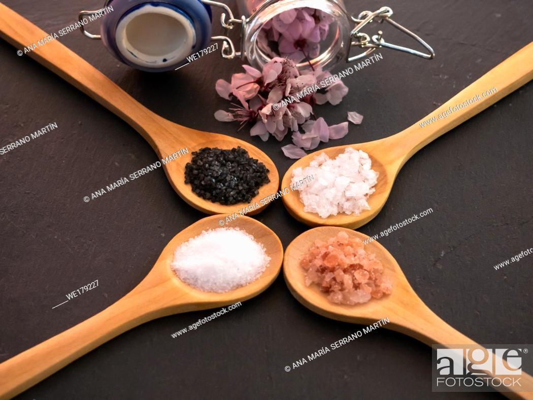 Stock Photo: Wooden spoons with himalayan salt, black hawaii salt, common salt and salt flakes on a slate plate.