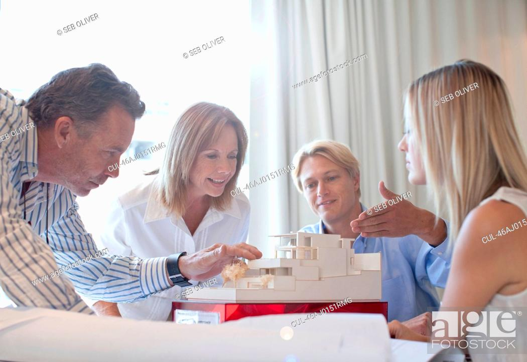 Stock Photo: Business people with model in office.