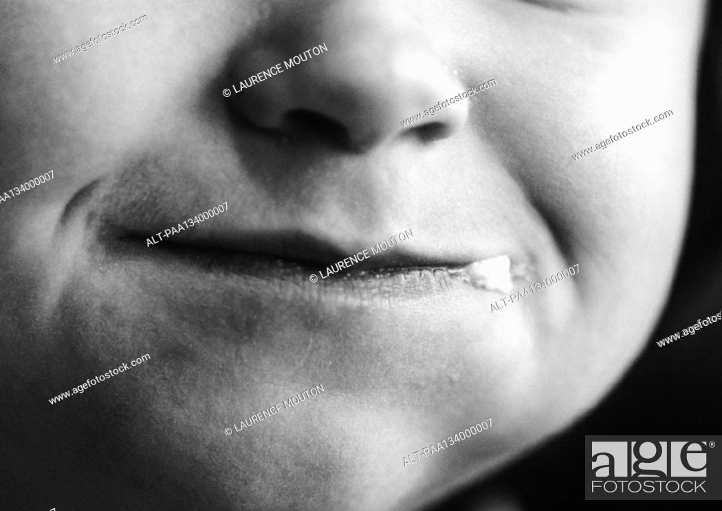 Stock Photo: Child's face, close-up on mouth, b&w.