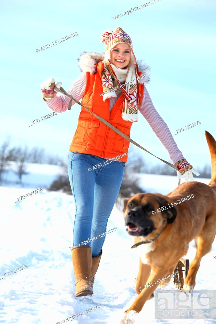 Stock Photo: young woman walking the dog in winter landscape.