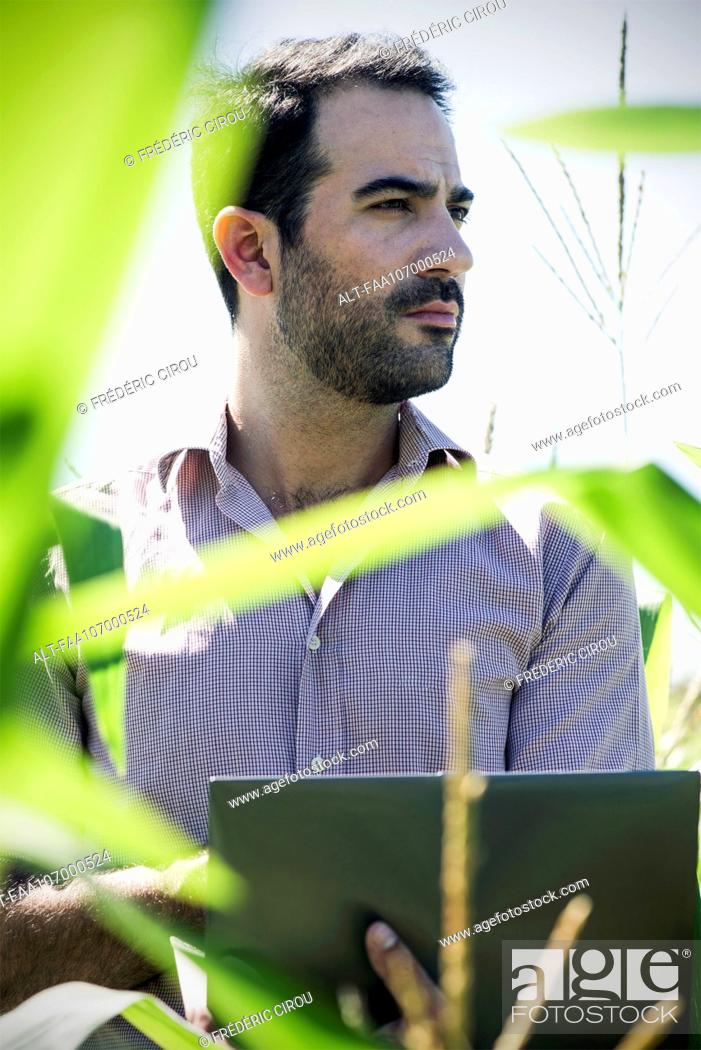 Imagen: Farmer using laptop computer while collecting data in cornfield.