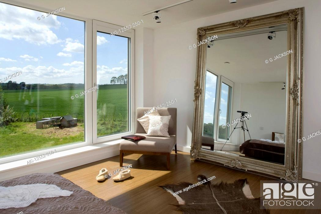 Stock Photo: Chair at window with oversized mirror in bedroom of carbon neutral home in Crossway, Kent, England.