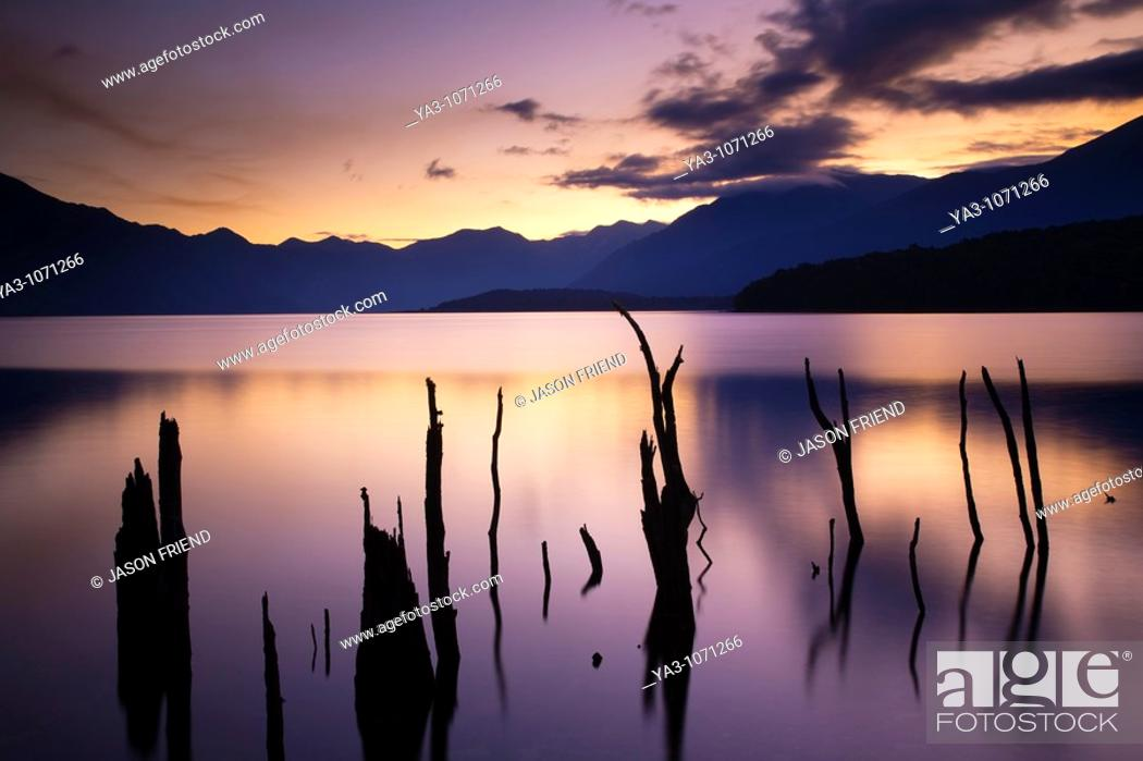 Stock Photo: New Zealand, Fiordland, Fiordland National Park  The flooded remnants of trees pierce the tranquil waters of Lake Monowai.
