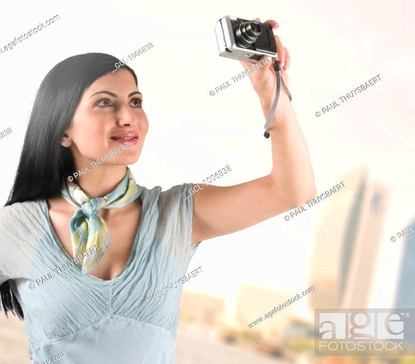 Stock Photo: Arab woman taking pictures of Dubai landmarks.