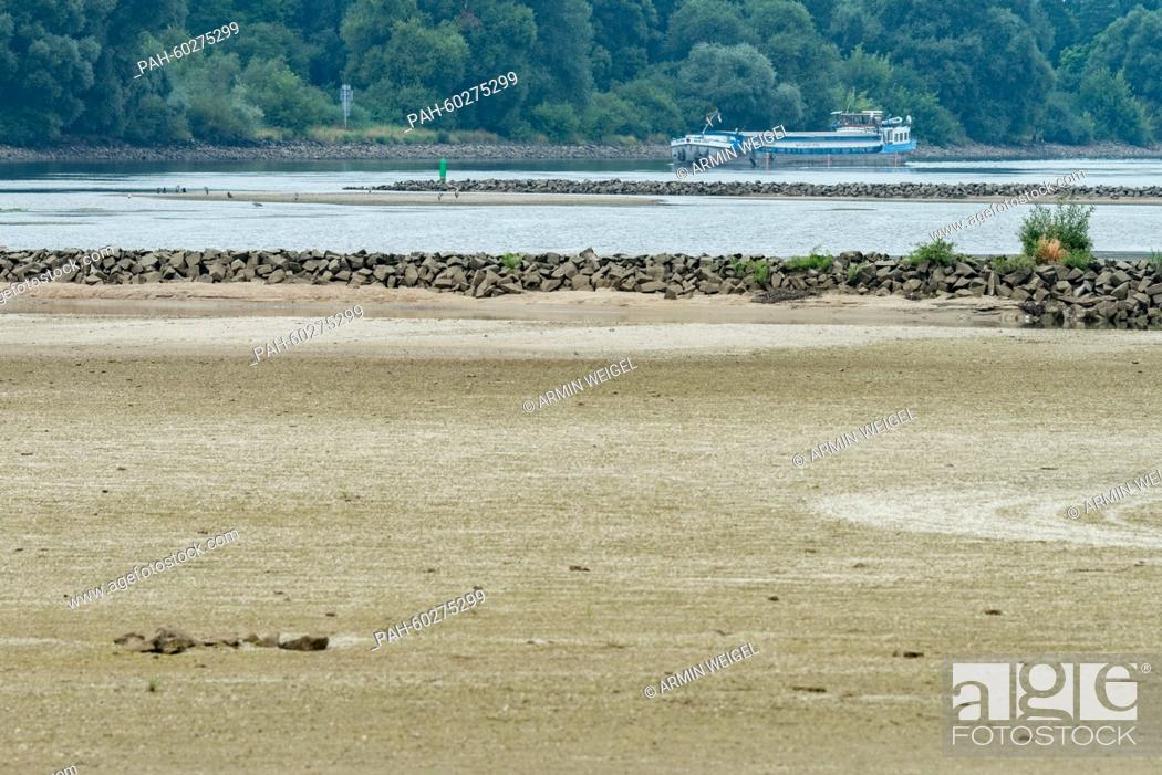 Stock Photo: A ship operates on the Danube river at low water near Mariaposching, Germany, 23 July 2015. The low water of the Danube due to the overdue rainfall interferes.