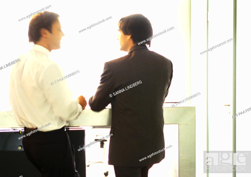 Stock Photo: Businessmen standing, talking side by side.