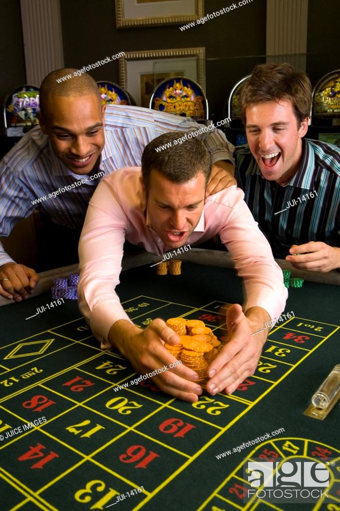 Stock Photo: Young man with friends collecting pile of gambling chips from roulette table in casino, smiling.