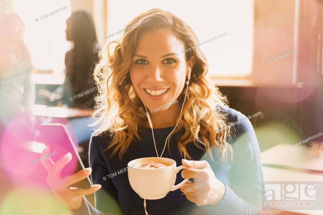Stock Photo: Portrait smiling woman with headphones listening to music on mp3 player and drinking cappuccino in cafe.
