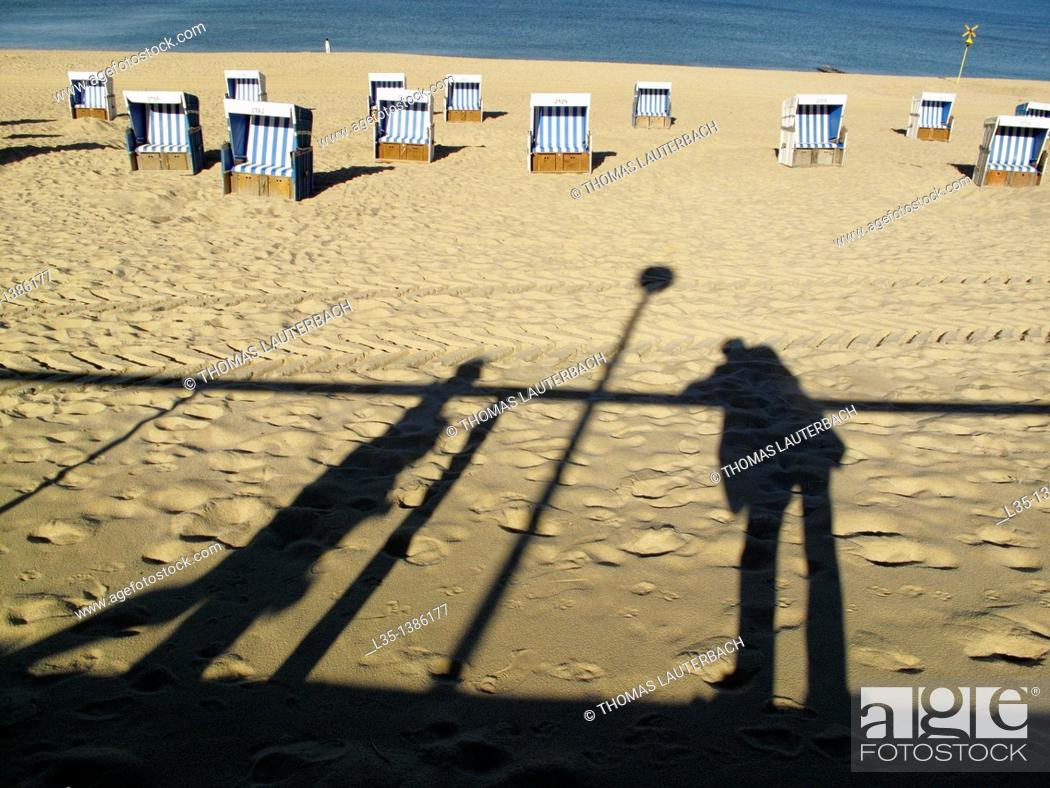 Stock Photo: Shadows of people on the beach of Westerland, beach chairs and the North Sea in the background, Sylt, Germany.