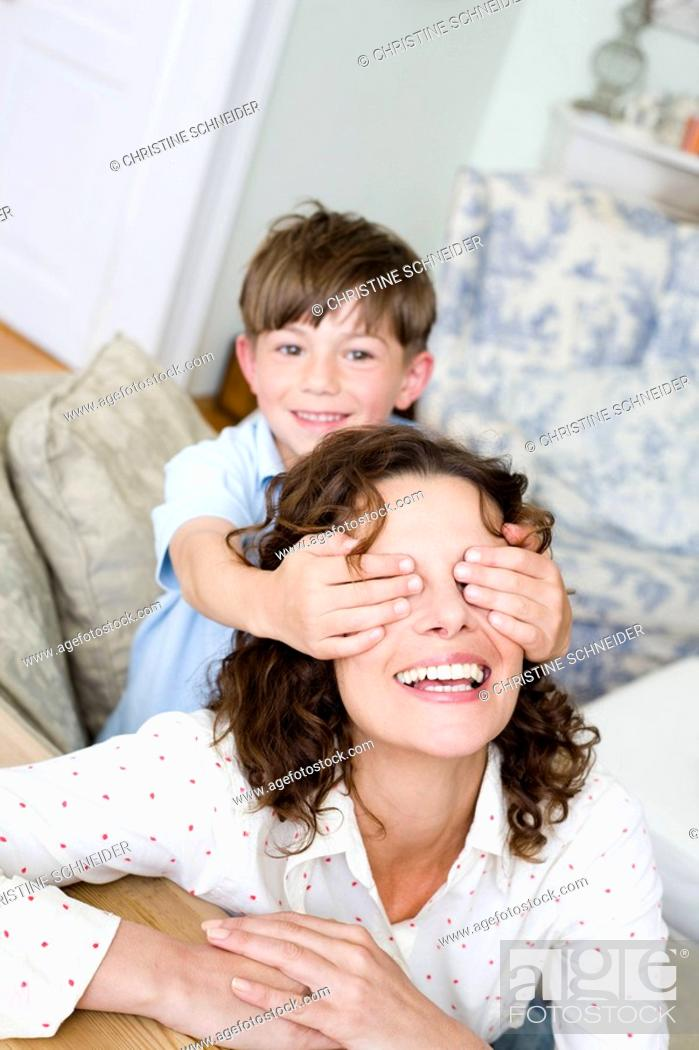 Stock Photo: Boy holding the eyes of his mum closed.