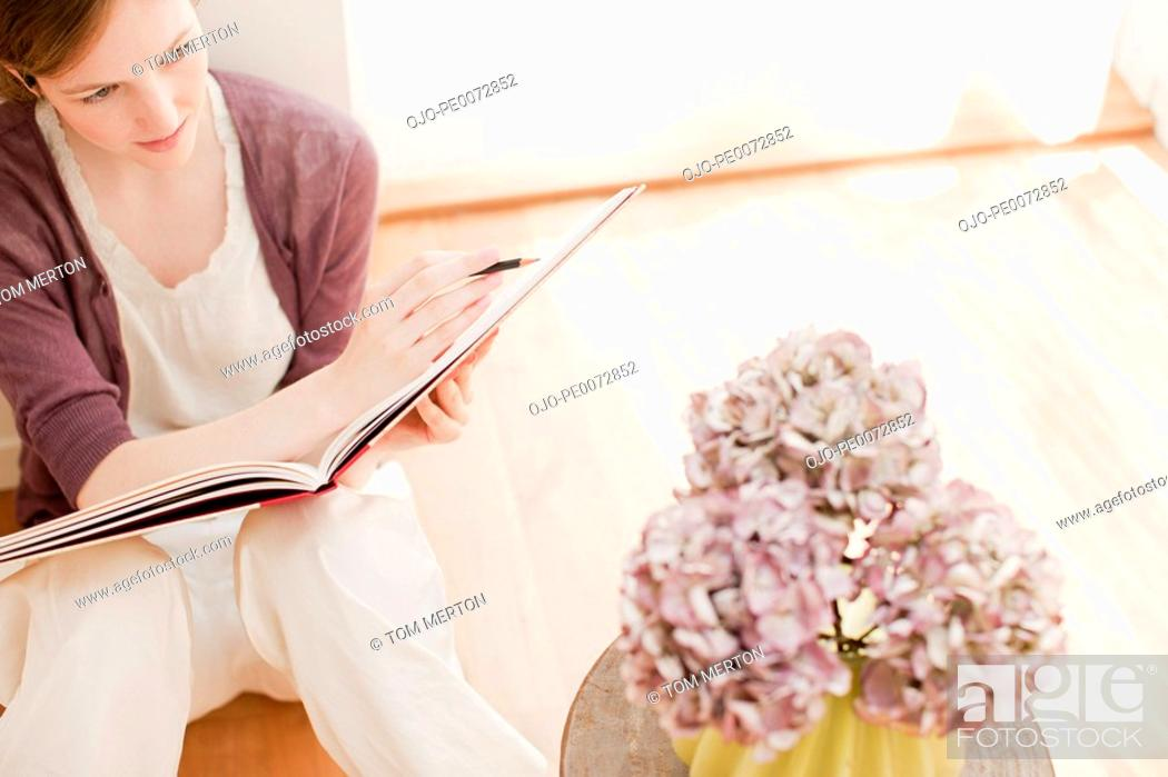 Stock Photo: Woman with sketch pad looking at flowers in vase.