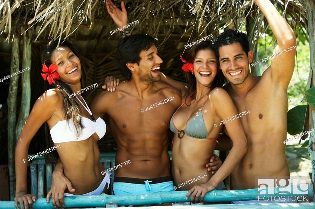 Stock Photo: Hispanic couples in beach hut.