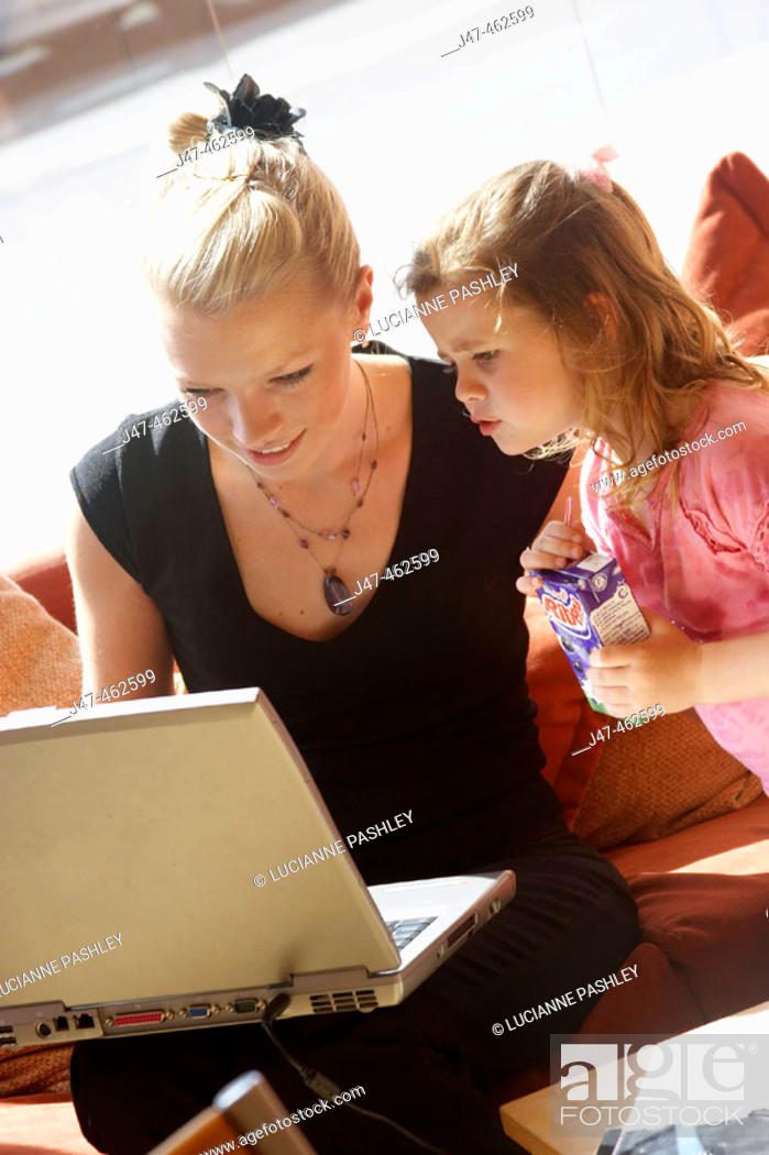Stock Photo: 21 year old girl working on a laptop on her knee, with a 3 year old girl watching.