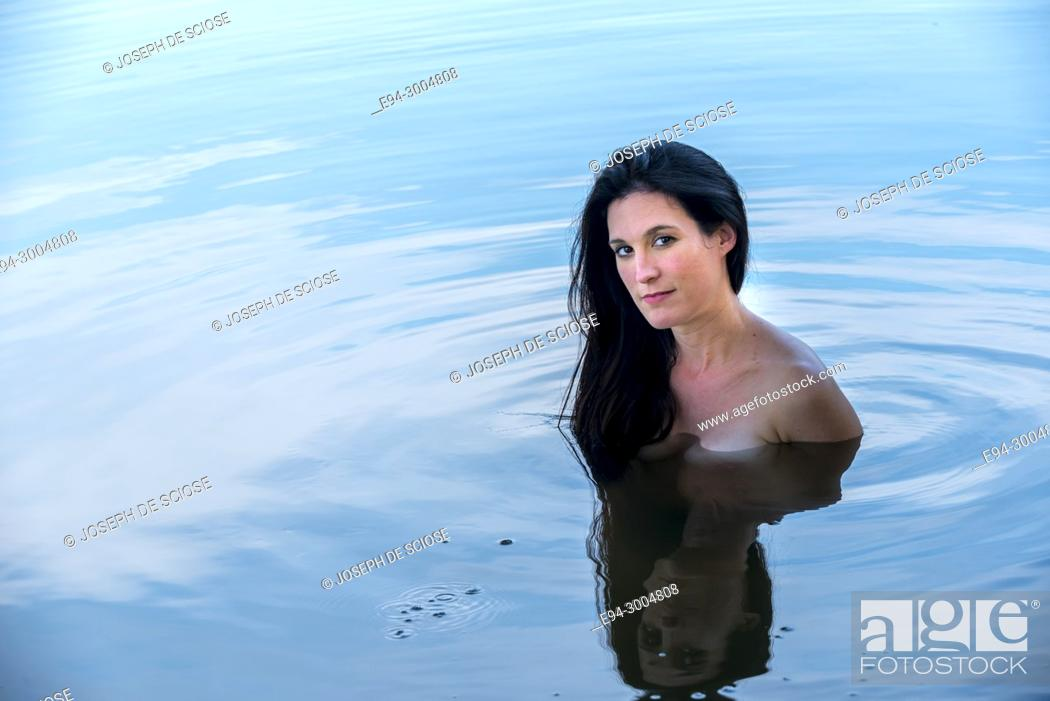 Stock Photo: A pretty partially nude 39 year old brunette woman looking at the camera, standing in a lake.