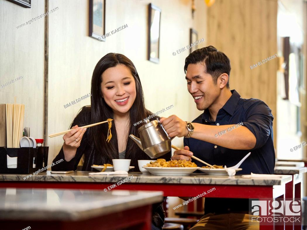 Stock Photo: Chinese man pouring tea for woman in restaurant.