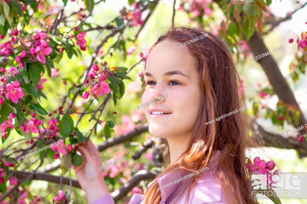 Stock Photo: Cute romantic young girl in an apple orchard in the springtime. Sunny spring day. Bright, peaceful, quiet, romantic atmosphere.