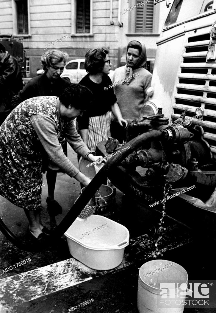 Stock Photo: Women queuing to get water. Some women with buckets and jerry cans, gathered around a firemen's tank truck; they are queuing for water and talking to each other.