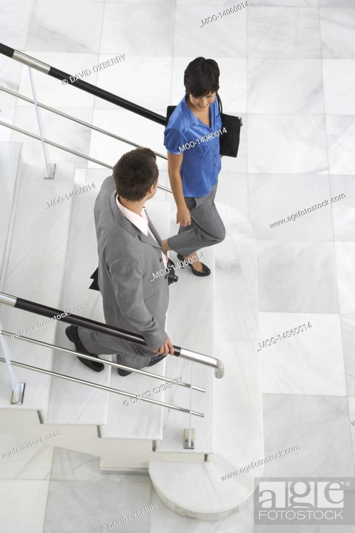 Stock Photo: Two business people walking down stairs.