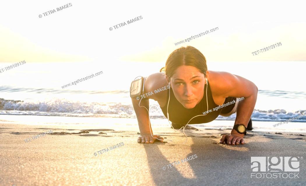 Stock Photo: Woman wearing headphones doing push-up on beach.