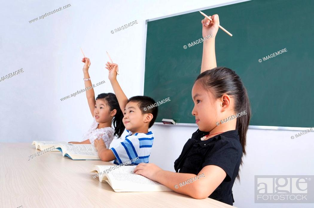 Stock Photo: Child, Three children learning in the classroom with hands raised.